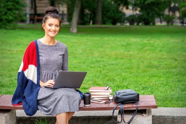 Piękna szczęśliwa młoda kobieta siedzi na ławce z laptopem w parku