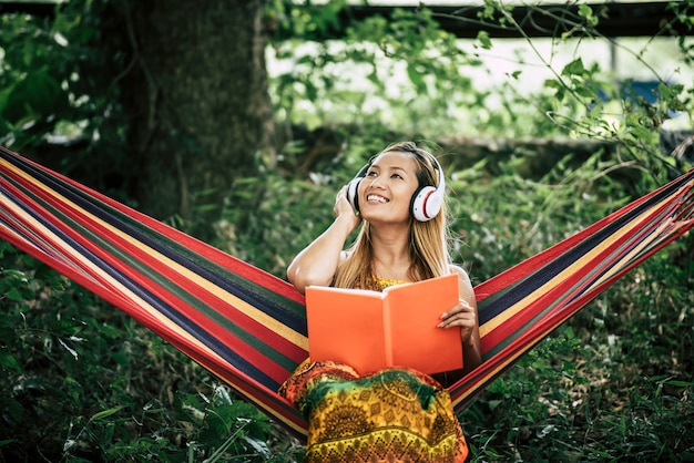 Piękna szczęśliwa młoda kobieta słucha muzyka i czytający książkę z hełmofonami