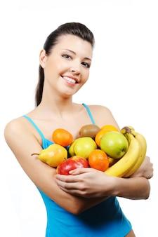 Piękna szczęśliwa młoda kobieta trzyma wiele owoców