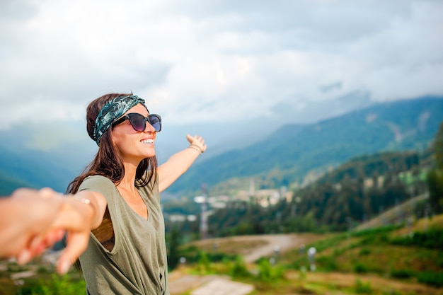 Piękna szczęśliwa młoda kobieta w górach w scenie mgła