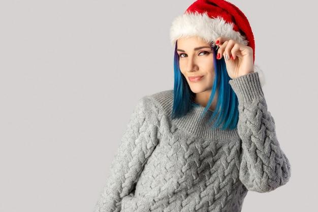 Piękna szczęśliwa młoda kobieta w santa hat na szarym tle. koncepcja sprzedaży świątecznych zakupów