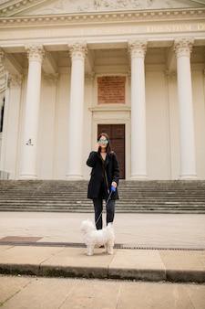 Piękna szczęśliwa młoda kobieta z cute mały pies szczeniak za pomocą telefonu komórkowego na ulicy w wiedniu, austria