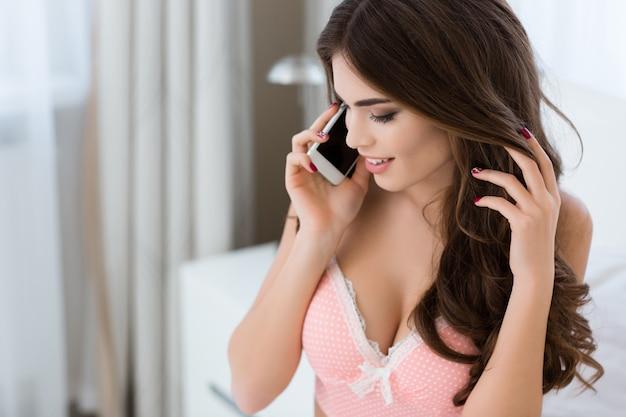 Piękna szczęśliwa młoda kobieta z długimi kręconymi włosami w różowej bieliźnie rozmawia przez telefon komórkowy w domu