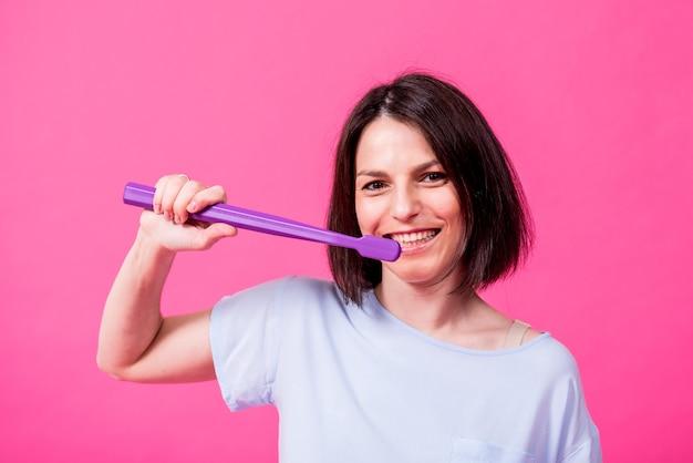 Piękna szczęśliwa młoda kobieta z dużą szczoteczką do zębów na pustym różowym tle