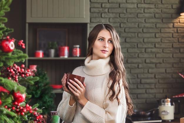 Piękna szczęśliwa młoda kobieta z uśmiechem na twarzy w kuchni w ozdób choinkowych