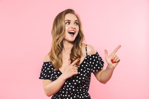 Piękna, szczęśliwa młoda ładna kobieta pozuje na białym tle na różowej ścianie pokazując copyspace
