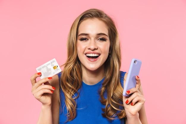 Piękna, szczęśliwa młoda, ładna kobieta pozuje odizolowana na różowej ścianie, trzymająca kartę kredytową za pomocą telefonu komórkowego