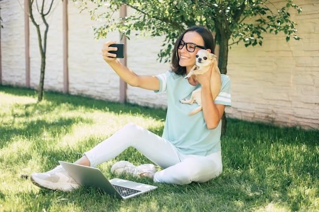 Piękna szczęśliwa młoda niezależna kobieta z małym słodkim psem pracuje na laptopie na świeżym powietrzu.