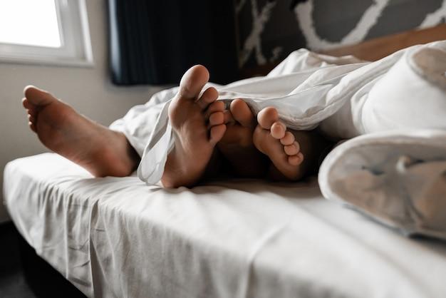 Piękna szczęśliwa młoda para lub rodzina budzi się razem w łóżku