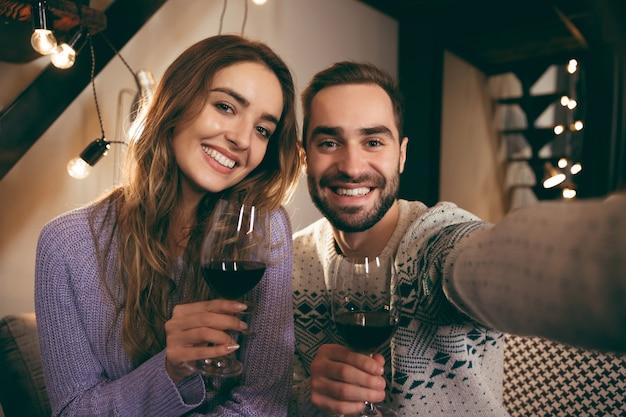 Piękna szczęśliwa młoda para spędza razem romantyczny wieczór w domu, pijąc czerwone wino, biorąc selfie