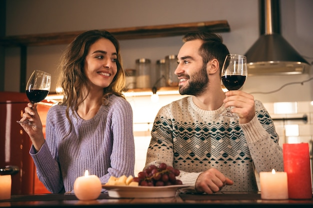 Piękna szczęśliwa młoda para spędza razem romantyczny wieczór w domu, pijąc czerwone wino, opiekania