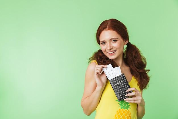 Piękna szczęśliwa młoda ruda dziewczyna pozuje na białym tle na tle zielonej ściany z paszportem i bilety.