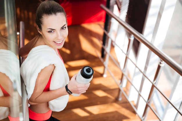 Piękna szczęśliwa młoda sportsmenka z białym ręcznikiem woda pitna w siłowni