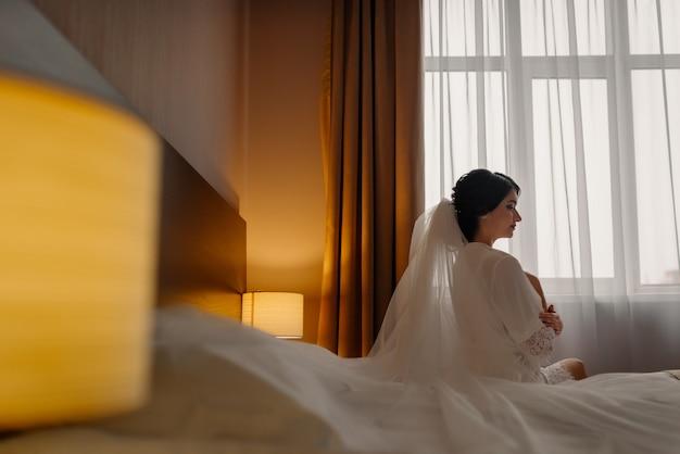 Piękna szczęśliwa panna młoda siedzi na łóżku. panna młoda z elegancką fryzurą i makijażem. dzień ślubu. piękno, panna młoda moda. najszczęśliwszy dzień ślubu.