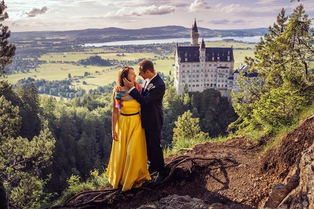 Piękna szczęśliwa para obejmuje się stojąc na górze na tle z niesamowitym widokiem, krajobraz z jeziorem, górami i ogromnym zamkiem. świętujemy rocznicę ślubu.