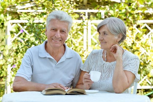 Piękna szczęśliwa para staruszków z drinkiem i książką w lecie