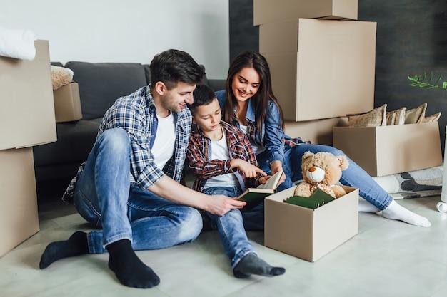 Piękna szczęśliwa rodzina o domu. przenoszenie koncepcji. szczęśliwa para z kartonem i synem czyta książkę