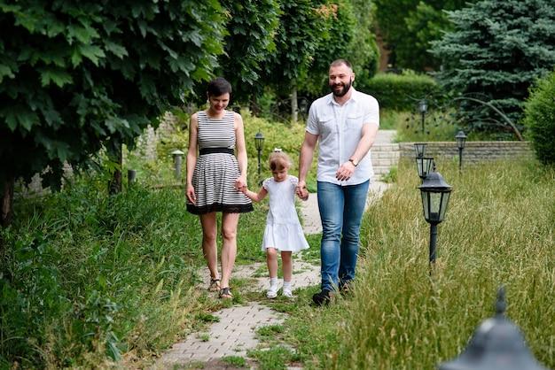 Piękna szczęśliwa rodzina w ciąży z córką w naturze