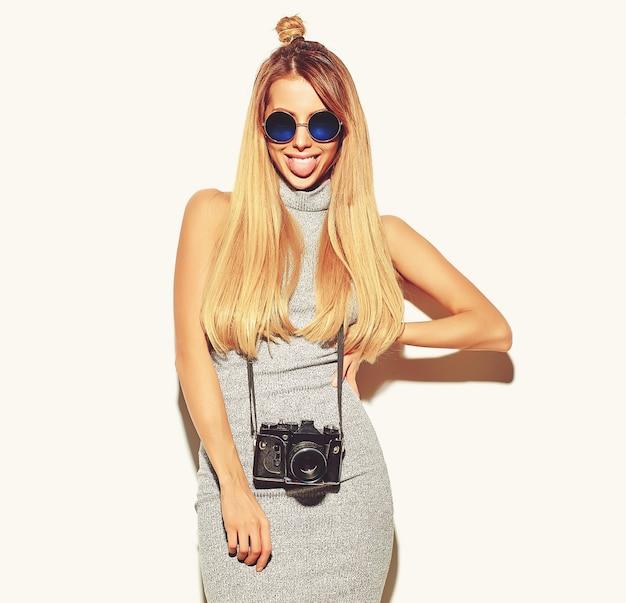 Piękna szczęśliwa śliczna blond kobieta w przypadkowych letnich ubraniach hipster robi zdjęcia, trzymając retro aparat fotograficzny na białym i pokazując jej język