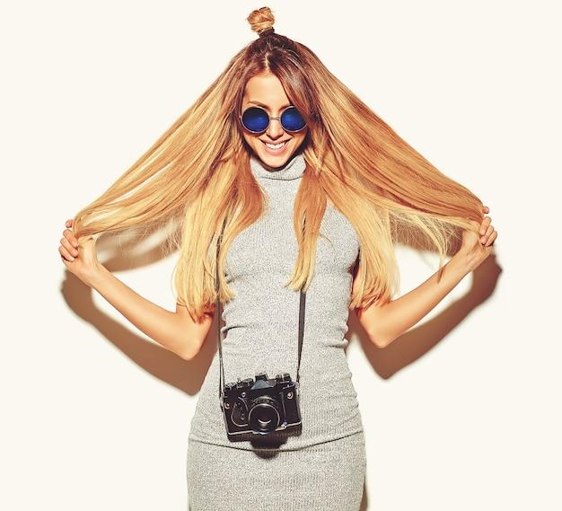 Piękna szczęśliwa śliczna blond kobiety dziewczyna w przypadkowym lata modnisia ubraniach robi fotografiom trzyma retro aparat fotograficzny odizolowywającego na bielu z włosy w rękach