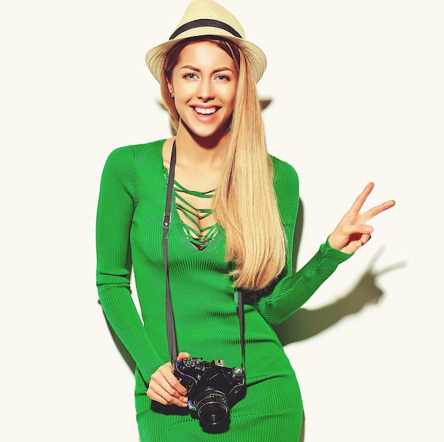 Piękna szczęśliwa śliczna blond kobiety dziewczyna w przypadkowym lato zieleni modnisia ubraniach robi fotografiom trzyma retro aparat fotograficzny