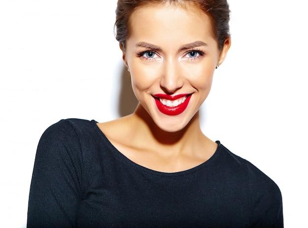 Piękna szczęśliwa śliczna seksowna brunetki kobieta w przypadkowej czerni sukni z czerwonymi wargami na biel ścianie