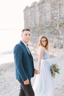 Piękna szczęśliwa ślub para fornal w niebieskiej kurtce i panna młoda w luksusowej błękit sukni chodzącym mieniu wręcza blisko jeziora garda. włochy, sirmione