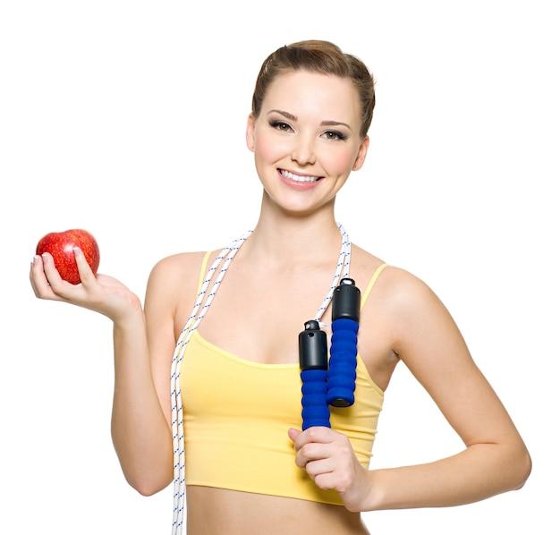 Piękna szczęśliwa sprawna kobieta z czerwonym jabłkiem i skakanka