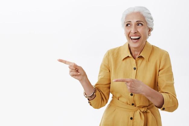 Piękna szczęśliwa starsza pani śmiejąca się i wskazująca palcami po lewej stronie reklamy