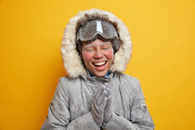Piękna szczęśliwa turystka cieszy się śnieżną zimą i uśmiecha się szeroko, splata dłonie ma twarz pokrytą lodem, spędza wolny czas w górach, nosi płaszcz, używa gogli narciarskich.