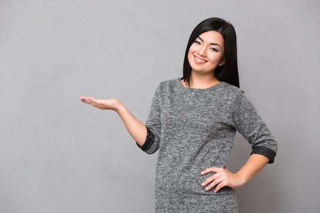 Piękna szczęśliwa uśmiechnięta azjatykcia kobieta w szarym swetrze patrząc na przód trzymając copyspace na dłoni