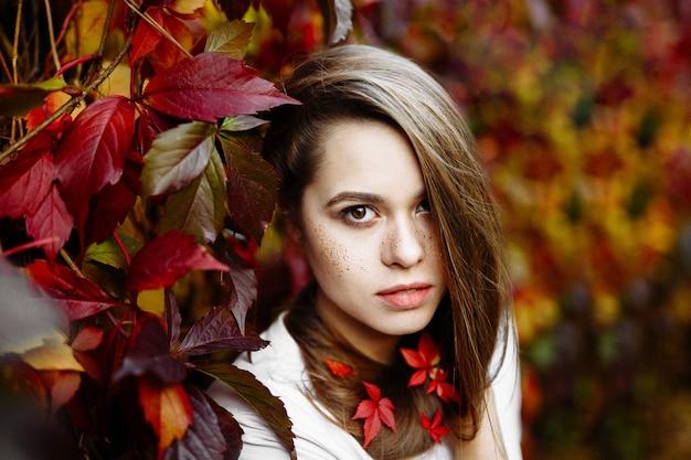 Piękna szczęśliwa uśmiechnięta dziewczyna z długimi włosami, pozuje na tle jesień liści w parku.