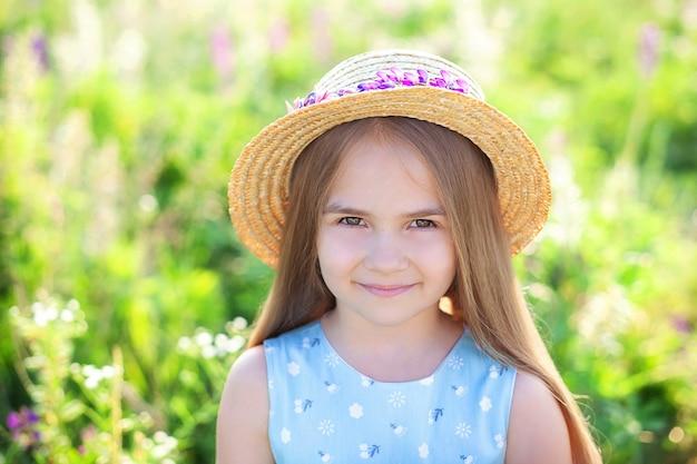 Piękna szczęśliwa uśmiechnięta dziewczynka z długimi włosami i słomkowym kapeluszem relaksująca na kwitnącym łubinie.