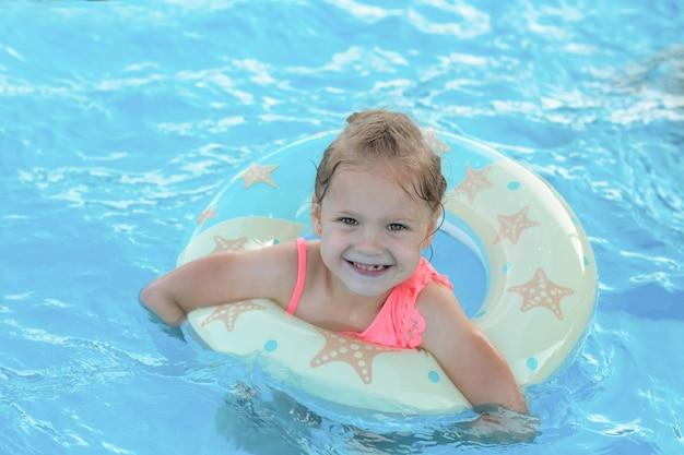 Piękna, szczęśliwa uśmiechnięta mała blondynka pływa w basenie na kole ratunkowym