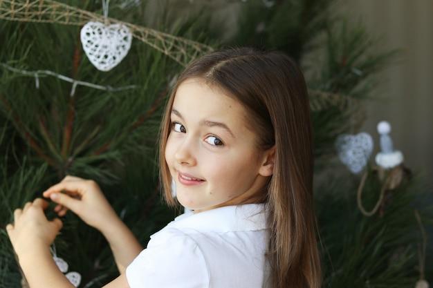 Piękna szczęśliwa uśmiechnięta mała dziewczynka dekoruje boże narodzenie białe dekoracje patrzeje