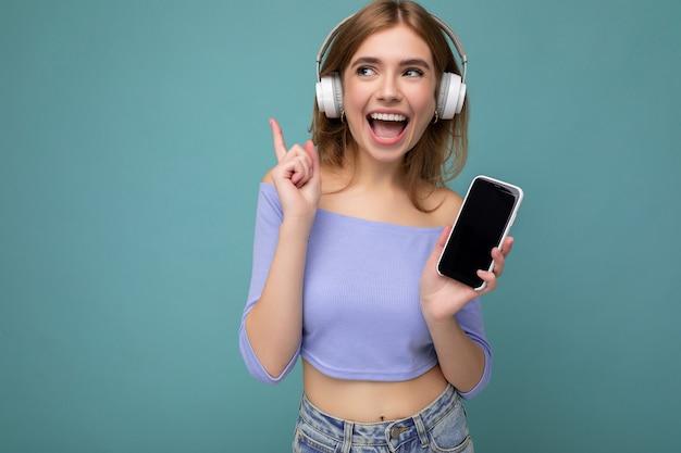 Piękna szczęśliwa uśmiechnięta młoda kobieta ubrana w stylowy strój casual na tle ściany