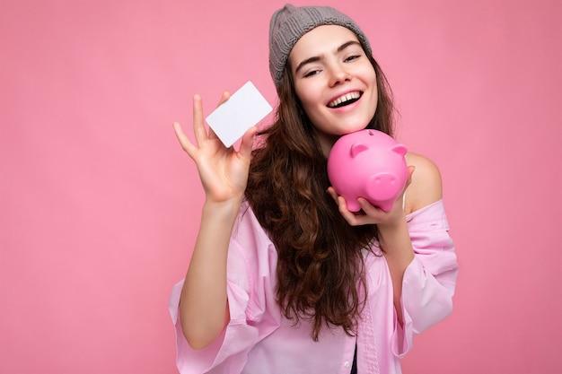 Piękna szczęśliwa uśmiechnięta radosna młoda kręcona brunetka ubrana w różową koszulę i szary kapelusz na białym tle
