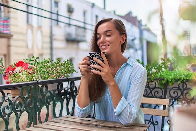 Piękna szczęśliwa uśmiechnięta romantyczna kobieta z zamkniętymi oczami, ciesząc się aromatyczną kawą na balkonie wczesnym rankiem w mieście