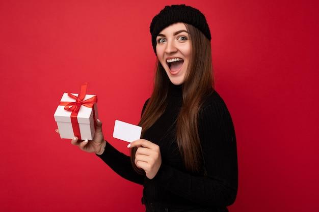 Piękna szczęśliwa zdziwiona młoda brunetka ubrana w czarny sweter i kapelusz odizolowane na czerwono
