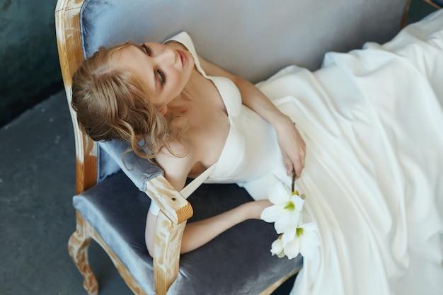 Piękna szczupła blondynka siedzi na kanapie w długiej białej sukni. portret kobiety z kwiatem w ręku