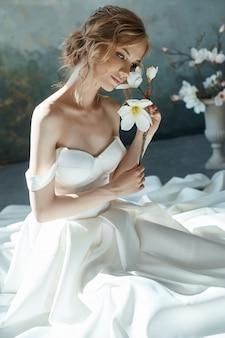 Piękna szczupła blondynka siedzi na podłodze w długiej białej sukni. portret kobiety z kwiatem w ręku, welon na twarzy