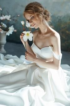 Piękna szczupła blondynka siedzi na podłodze w długiej białej sukni.