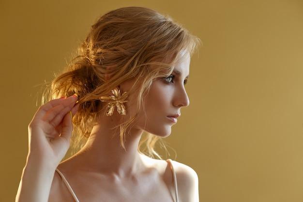 Piękna szczupła blondynka w wieczornym słońcu w długiej białej sukni. portret kobiety z kwiatem. perfekcyjna fryzura i kosmetyki panny młodej, nowa kolekcja sukien ślubnych