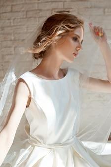 Piękna szczupła blondynka w wieczornym słońcu w długiej białej sukni. portret kobiety z kwiatem w dłoni