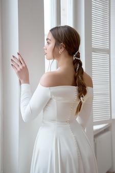 Piękna szczupła blondynka w wieczornym słońcu w długiej białej sukni w pobliżu dużego okna. idealne fryzury i makijaż dla panny młodej, nowa kolekcja sukien ślubnych