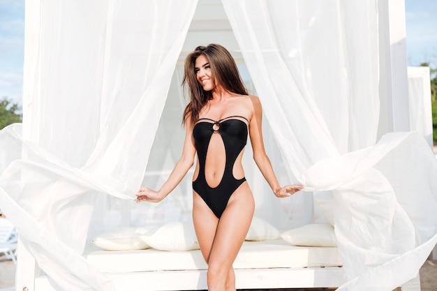 Piękna szczupła brunetka dziewczyna pozuje w stroju kąpielowym z długimi włosami, siedząc na łóżku na plaży nad brzegiem morza