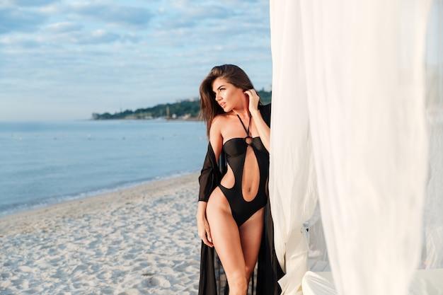 Piękna szczupła brunetka dziewczyna pozuje w stroju kąpielowym z długimi włosami w pobliżu łóżka na plaży nad brzegiem morza