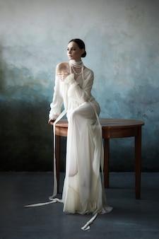Piękna szczupła brunetka dziewczyna siedzi na kanapie w długiej białej sukni. portret kobiety z biżuterią na szyi. perfekcyjna fryzura i kosmetyki kobiety, nowa kolekcja lekkich sukienek