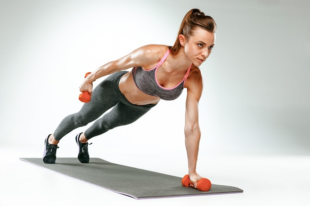 Piękna szczupła brunetka robi ćwiczenia rozciągające