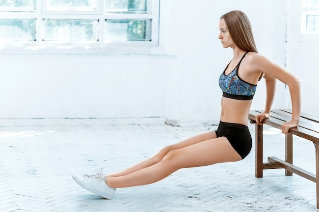 Piękna szczupła brunetka robi kilka pompek na siłowni